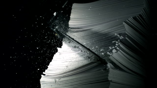 Chainsaw cutting pile of book, Slow Motion video
