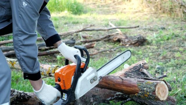 kettensägen-start. ein mann in grauen overalls schneidet ein holz mit einer kettensäge - brennholz stock-videos und b-roll-filmmaterial