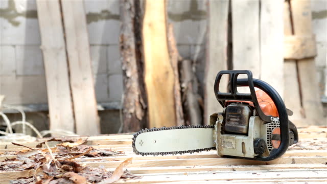 Chainsaw on wooden planks. video