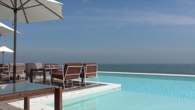 стул и зонтик с бассейном и океанским морским пляжем фон - space background стоковые видео и кадры b-roll