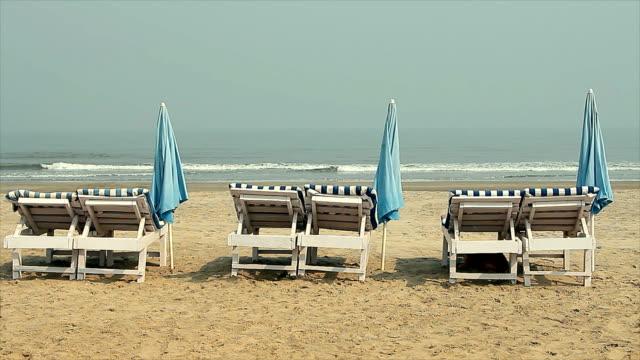 stuhl mit regenschirm in der nähe des strandes - sonnenschirm stock-videos und b-roll-filmmaterial