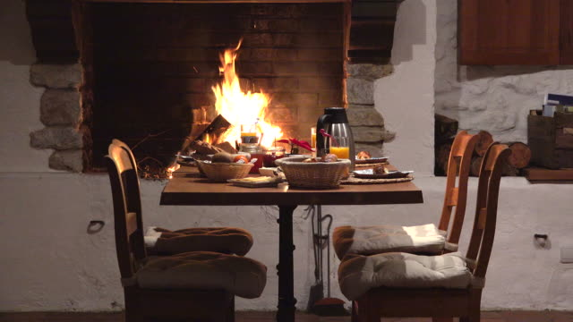 Chairs and table near fireplace, delicious meal preparation, wait for lovers couple, romantic dinner, exquisite cuisine
