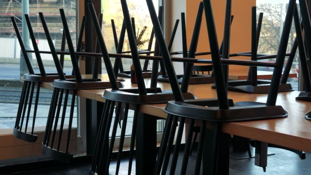 Chairs on tables in a closed cafe, cars drive outside windows in the background