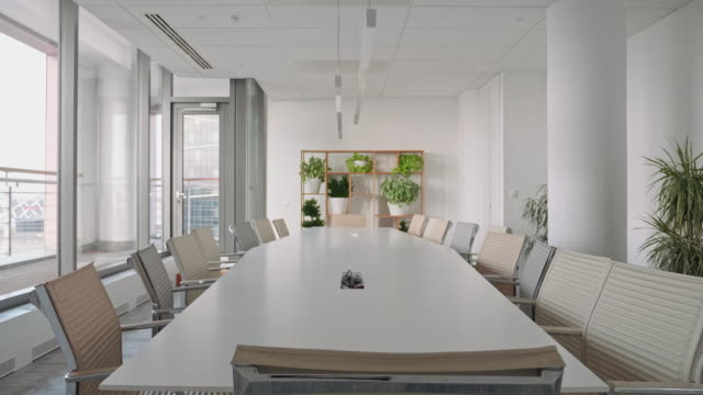 vídeos de stock e filmes b-roll de chairs surrounding conference table in office board room - sala