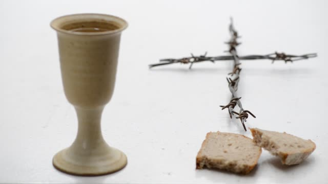 vídeos de stock e filmes b-roll de chalice of wine with bread and crucifix  on the table. rack focus. - cálice equipamento religioso