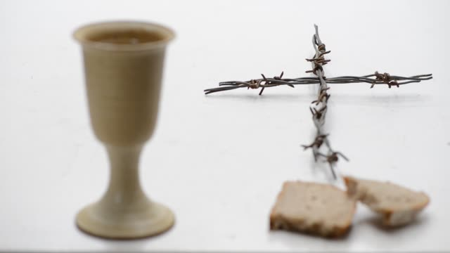 vídeos de stock e filmes b-roll de chalice of wine with bread and crucifix  on the table. rack focus. - comunhão