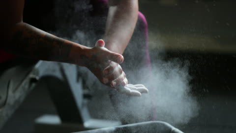 Chalking Up, Ready to Lift Weights Close up shot of an unrecognisable woman clapping his hands together as he chalks up ready to lift weights in the gym. endurance stock videos & royalty-free footage