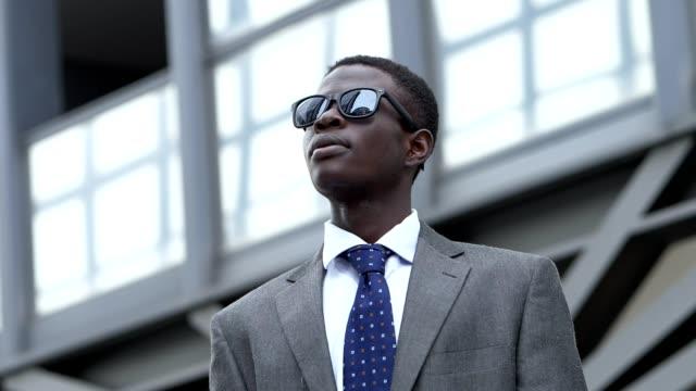 vídeos de stock, filmes e b-roll de desafio, sucesso, negócios. juventude negra homem de negócios bem-sucedido na rua - moda urbana