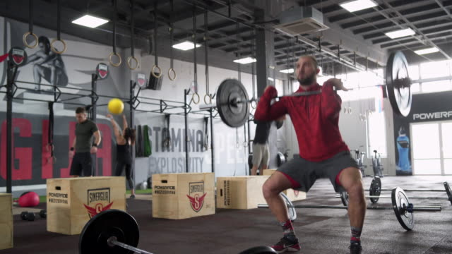 Challenging myself Group of athletes working out in the gym, doing deadlifts cross training stock videos & royalty-free footage