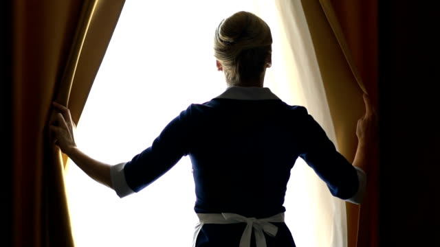 chambermaid of luxury hotel opening curtains in best suit, going to clean room - kurort turystyczny filmów i materiałów b-roll
