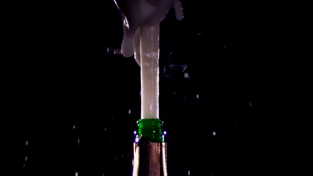 Champagne bottle is opened and sprinkled. Slow motion, black background Champagne bottle is opened and sprinkled, bottle visible is not completely only the neck, plug opens man and wine lathers, foam is rises up, side view, slow motion, black background soda stock videos & royalty-free footage