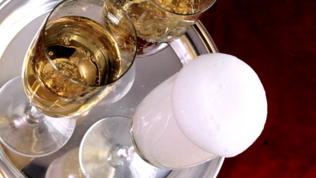Champagne celebration Bottle of champagne comes into frame and fills 3 flutes on silver tray tray stock videos & royalty-free footage