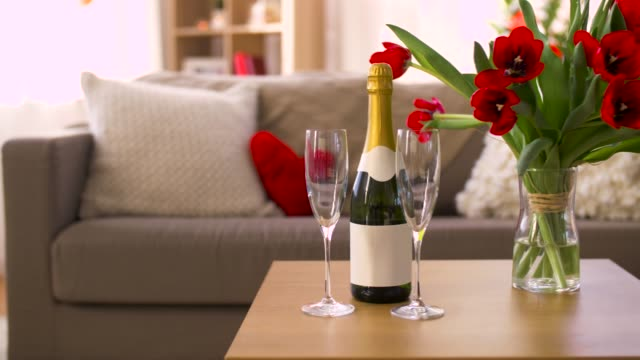 champagne, glasses and flowers at valentines day valentines day, romantic date and holidays concept - bottle of champagne, two glasses and red tulip flowers on table in living room or home valentines day stock videos & royalty-free footage
