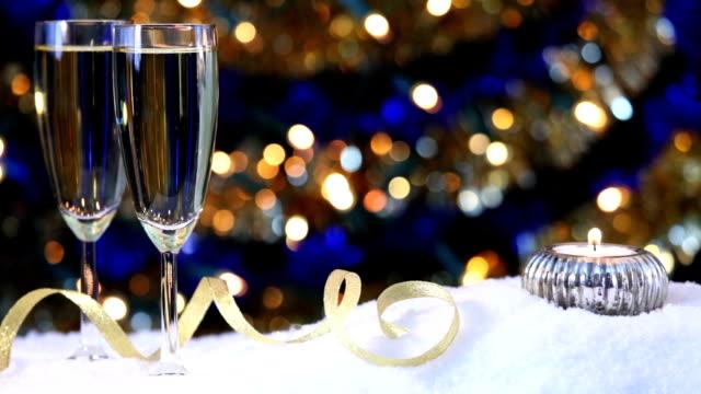 vidéos et rushes de verres de champagne sur la neige avec lumières vacillantes de l'arrière-plan - flûte à champagne