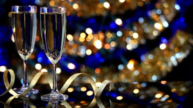 vidéos et rushes de verres de champagne avec lumières de noël à l'arrière-plan - flûte à champagne