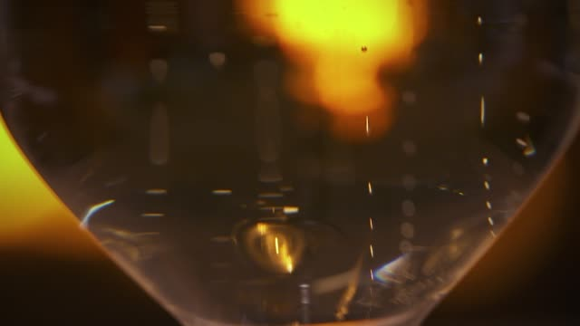 champagne in a transparent glass with a black background. we can see the golden bubbles ot the bottom of the glass - close-up view - drinking concept - happy hour video stock e b–roll
