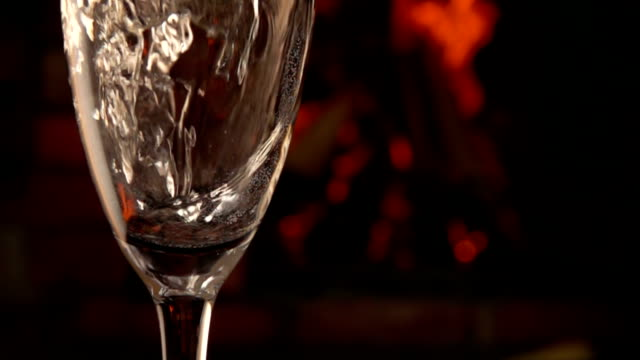 Champagne is poured into a glass on a background of fire video