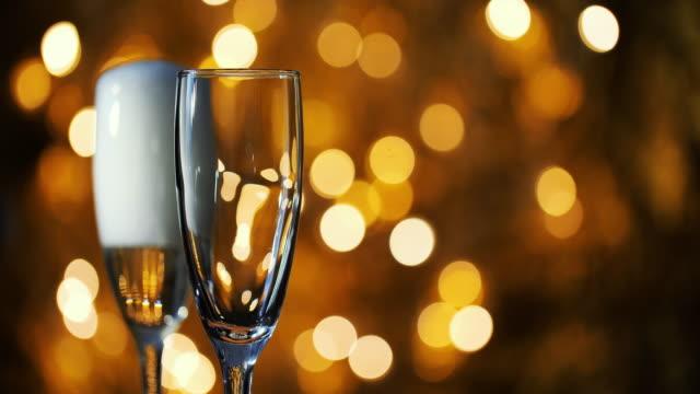 champagner wird vor dem hintergrund der neujahrsgirlande in gläser gegossen. - champagner toasts stock-videos und b-roll-filmmaterial