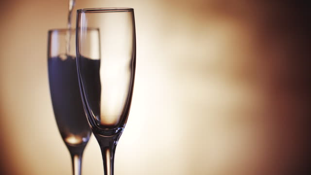 champagner wird in die gläser gegossen. zeitlupe. 4k. - champagner toasts stock-videos und b-roll-filmmaterial