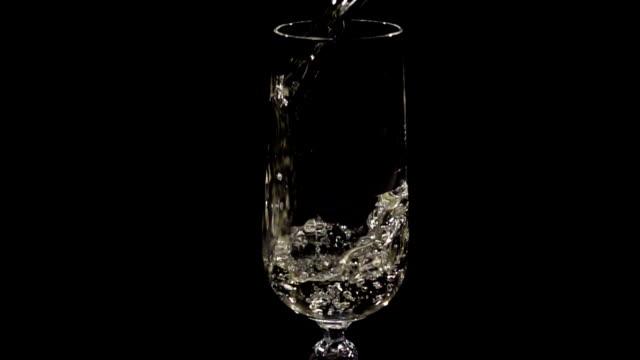vidéos et rushes de champagne ou vin blanc versé dans le verre au ralenti - flûte à champagne