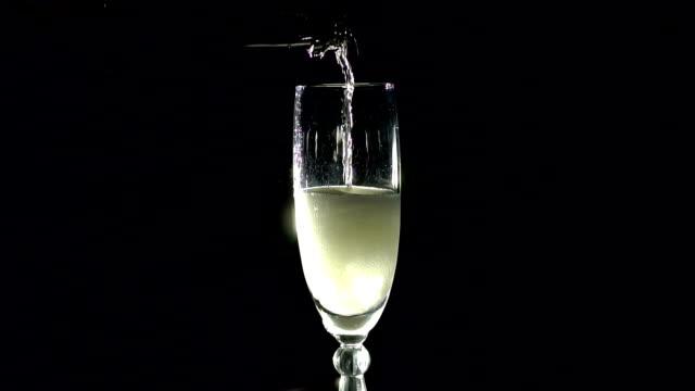vidéos et rushes de champagne, verser dans le verre d'une bouteille dans l'obscurité. - champagne