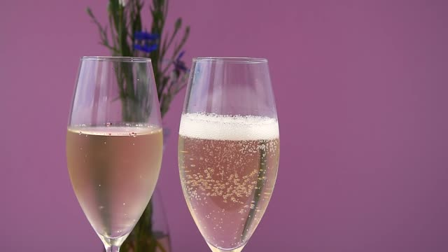 Champagne. Two Flutes with Sparkling Wine over Purple Background. Pouring champagne.