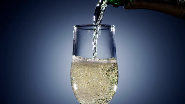 Champagne wine is poured into transparent glass tumbler from bottle video