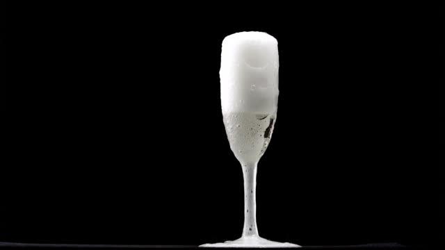 vidéos et rushes de champagne avec des bulles est coulée dans un verre classique sur fond noir - flûte à champagne