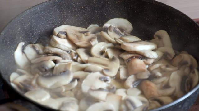 Champignon mushrooms are fried in a frying pan video