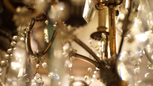 Chandelier luxury on crystals and gold. ECU Hand-held Camera and selective focus with film color grading. Use for background clip or insert shot : Chandelier luxury on crystals and gold. 19th century style stock videos & royalty-free footage