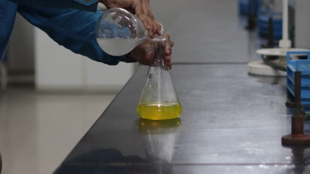 change in color of a yellow chemical in conical flask on addition of a white chemical from a conical flask in a chemistry lab.