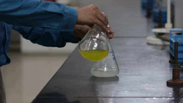 change in colour of a white chemical in conical flask on addition of a white chemical from a conical flask in a chemistry lab.