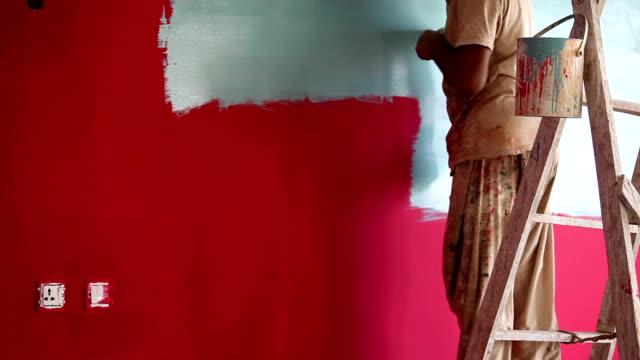 change of mind, painter painting pale color over red wall - painting wall bildbanksvideor och videomaterial från bakom kulisserna