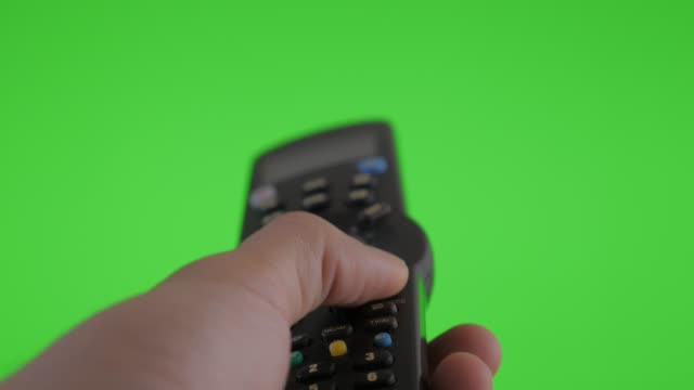 changing channels with remote control in front of green screen 4k - television industry stock videos & royalty-free footage