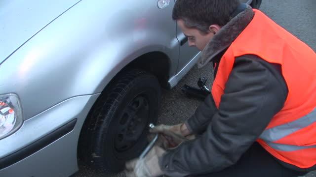 vídeos de stock e filmes b-roll de hd: mudar o pneu - berma da estrada
