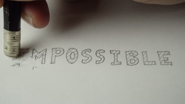 Changing the word impossible to possible. Impossible word gets the ''im'' removed to make it possible. Pencil erase it to possible. 4K Resolution.