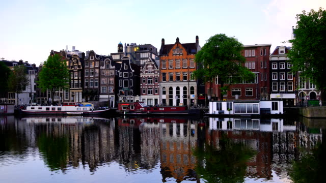 channel in downtown amsterdam netherlands at twilight - canale video stock e b–roll