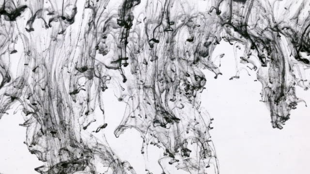 Chaotic movement of drops of black paint in water. Ink in water. Close-up.