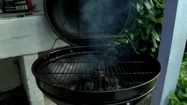 charcoal bbq in action. waiting for the charcoal to burn white and ready to cook upon. - coperchio video stock e b–roll