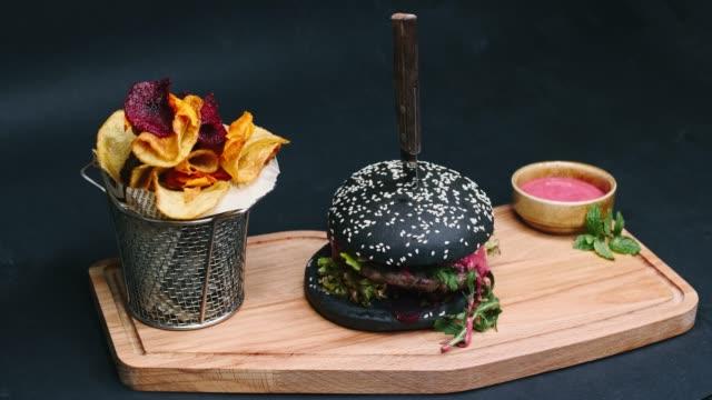 보드, 칼, 피어 싱과 슬로우 모션 챔버 통로에서 4 k 해상도에 먹을 준비가 숯 햄버거 감자 튀김와 붉은 소스는 - burger and chicken 스톡 비디오 및 b-롤 화면