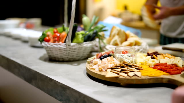 Charcuterie Board and kitchen staff preparing food Different types of cheese, meet and olives on wooden board in kitchen plank timber stock videos & royalty-free footage