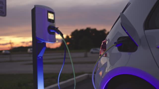 vídeos de stock e filmes b-roll de slo mo charging a car at charging station at dusk - carregar