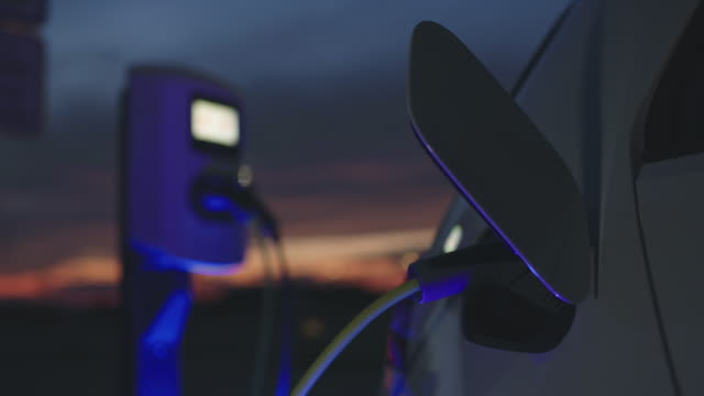 slo mo charging a car with blue energy at dusk - carica elettricità video stock e b–roll