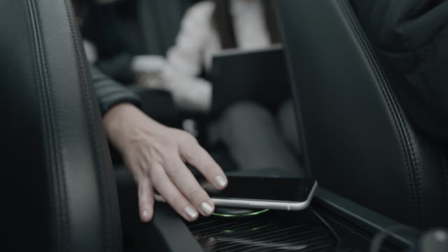 MS Charging a smartphone on a wireless charger in the car
