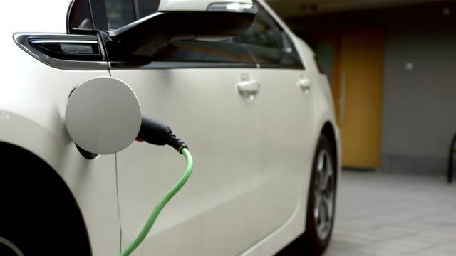 hd: ricarica un'auto elettrica a casa - carica elettricità video stock e b–roll