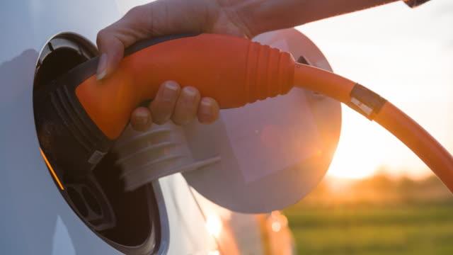 charging electric car at sunrise in green outdoors - sostenibilità video stock e b–roll
