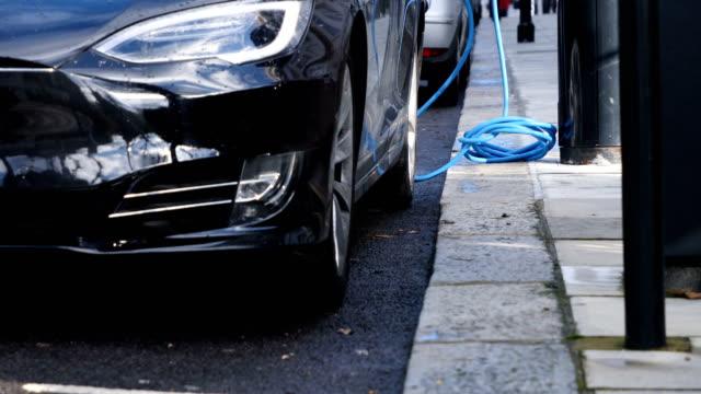elektroauto auf der straße aufgeladen - elektromobilität stock-videos und b-roll-filmmaterial