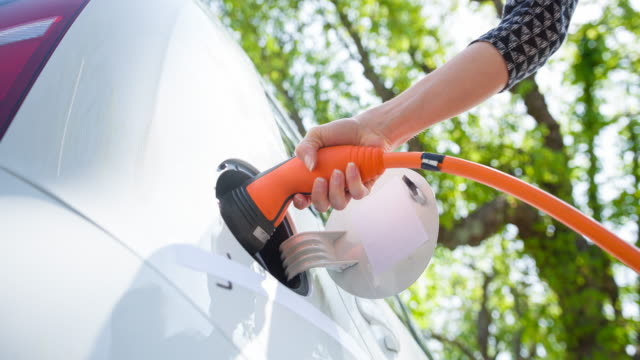 vídeos de stock e filmes b-roll de charging electric car under green trees - carregar