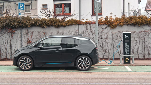 charging modern electric car on the street which are the future of automobile - carica elettricità video stock e b–roll
