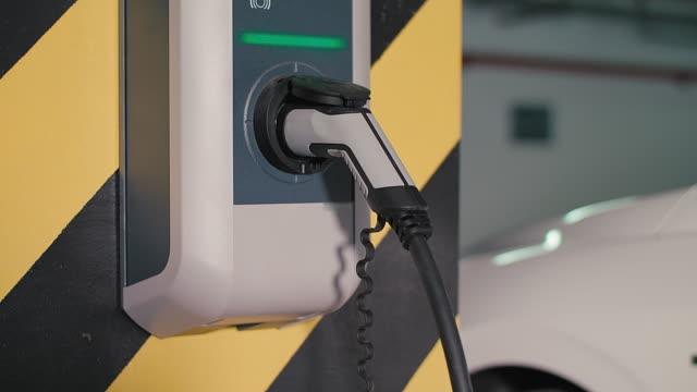 charging of an electric car - carica elettricità video stock e b–roll